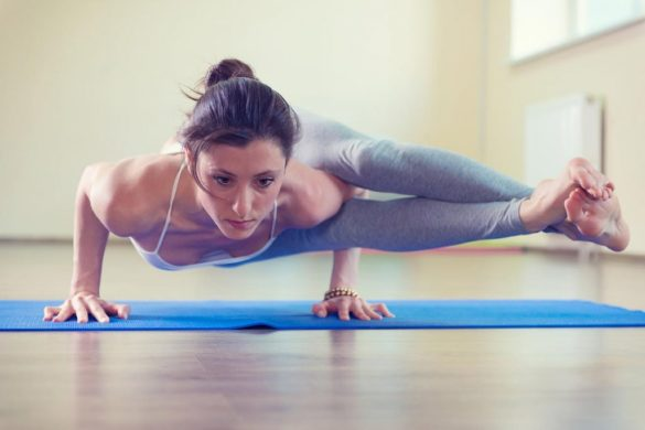 woman doing intense yoga pose on yoga mat